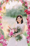 Happy smiling bride with great flower bouquet is sitting in the wedding peonies arch in the sunny park. Happy smiling bride with great flower bouquet is sitting Royalty Free Stock Image