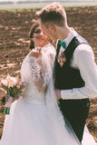 Happy smiling bride with groom on field Royalty Free Stock Image