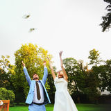 Happy smiling bride and groom hands releasing white doves on a s Royalty Free Stock Image