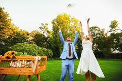 Happy smiling bride and groom hands releasing white doves on a s Stock Photography