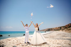 Happy smiling bride and groom hands releasing white doves on a sunny day.  Mediterranean Sea. Cyprus Stock Images