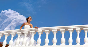 Happy Smiling Bride in a Long Veil Standing on the Terrace. At the blue sky Stock Photos