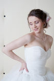Happy smiling bride in white dress near wall Royalty Free Stock Images