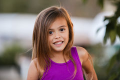 Happy and smiling brown haired girl. Pretty four year old girl with brown hair is smiling.   She is wearing a purple tank top.  Bokeh in background Stock Photo