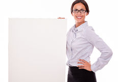 Happy smiling brunette businesswoman with placard. Happy brunette businesswoman with glasses looking at the camera, smiling, holding a placard, wearing her Royalty Free Stock Image