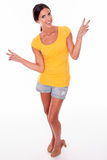 Happy smiling brunette gesturing peace sign. Happy smiling brunette woman gesturing peace signs while looking at camera and wearing a yellow t-shirt and short Stock Photography