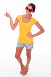 Happy smiling brunette with red sunglasses. Happy brunette gesturing and hand on hip looking at the camera while wearing a yellow t-shirt, short jeans and red Stock Image