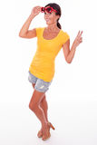 Happy smiling brunette with red sunglasses. Happy brunette gesturing a peace sign, peeping at the camera while wearing a yellow t-shirt, short jeans and red Royalty Free Stock Photos