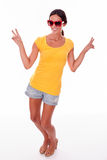 Happy smiling brunette with red sunglasses. Happy brunette gesturing peace signs looking at the camera while wearing a yellow t-shirt, short jeans and red Royalty Free Stock Image