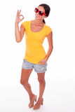 Happy smiling brunette with red sunglasses. Happy brunette gesturing perfect a sign looking at the camera while wearing a yellow t-shirt, short jeans and red Stock Photo