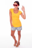 Happy smiling brunette with red sunglasses. Happy brunette gesturing perfect a sign looking at the camera while wearing a yellow t-shirt, short jeans and red Stock Photography