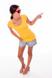 Happy smiling brunette with red sunglasses. Happy brunette pointing and looking to her left while wearing a yellow t-shirt, short jeans and red sunglasses on a Stock Photo