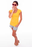 Happy smiling brunette with red sunglasses. Happy brunette touching her face while looking at the camera and wearing a yellow t-shirt, short jeans and red Royalty Free Stock Photo