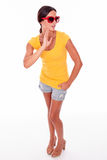 Happy smiling brunette with red sunglasses. Happy brunette touching her face while looking at the camera and wearing a yellow t-shirt, short jeans and red Stock Photo
