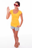 Happy smiling brunette with red sunglasses. Happy brunette waving and looking at the camera while wearing a yellow t-shirt, short jeans and red sunglasses on a Stock Photos