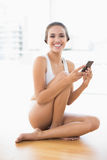 Happy smiling brunette woman sitting on the floor and holding a mobile phone Stock Photography