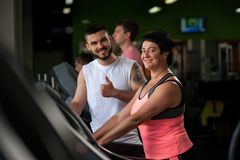 Happy smiling brunette woman and fitness coach. Happy smiling brunette women and male fitness coach standing on treadmill zone and looking at the camera. Middle Stock Photos