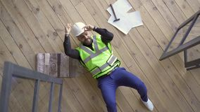 Happy smiling builder in the helmet and green jacket lying on the floor showing victory gestures and looking up. Profession concept. The guy resting after work stock video footage