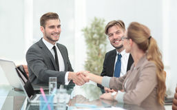 Happy smiling business people shaking hands after a deal in offi Royalty Free Stock Image