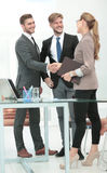 Happy smiling business people shaking hands after a deal in offi. Business people closing a deal and handshaking at the office Royalty Free Stock Photos