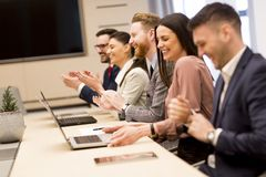 Happy smiling business team clapping hands during a meeting in o. Happy smiling business team clapping hands during a meeting in the office Stock Images