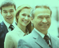 Happy smiling business team standing in a row at office Stock Image