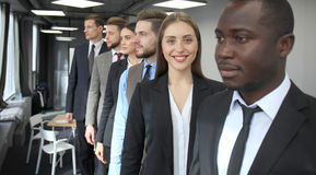 Happy smiling business team standing in a row at office. Stock Image