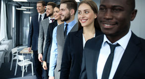 Happy smiling business team standing in a row at office. Stock Photos