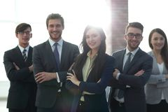 Attractive young business owner in office, folded hands  in fron. Happy smiling business team standing in a row at office Royalty Free Stock Photos