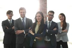 Attractive young business owner in office, folded hands  in fron. Happy smiling business team standing in a row at office Stock Photography