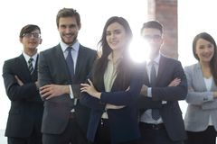 Attractive young business owner in office, folded hands  in fron. Happy smiling business team standing in a row at office Stock Image