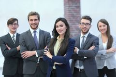 Attractive young business owner in office, folded hands  in fron. Happy smiling business team standing in a row at office Stock Photo