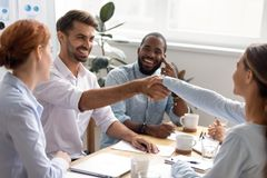 Happy smiling businessman businesswoman shaking hands at business meeting. Happy smiling businesswoman shaking hands at partners meeting. Colleagues thanking royalty free stock photography