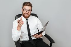Happy smiling businessman in eyeglasses holding folder. And pointing at camera while sitting in chair  over gray background Royalty Free Stock Photo