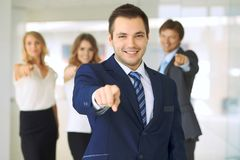 Happy smiling businessman and his colleagues pointing by finger into the camera. Concept of employer and success team.  Royalty Free Stock Photography