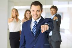 Happy smiling businessman and his colleagues pointing by finger into the camera. Concept of employer and success team.  Stock Image