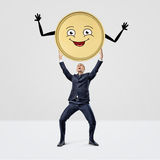 A happy smiling businessman holding a large golden coin with a smiley face over his head. Royalty Free Stock Images