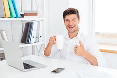 Happy smiling businessman holding tea cup and showing thumbs up Stock Photos