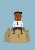 Happy smiling businessman on money bags. Joyful smiling businessman sitting on money bags. Financial success, prosperity and wealth concept Royalty Free Stock Photography