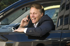 Happy smiling businessman on phone. A handsome forties businessman is enjoying a lighthearted conversation on his cellphone while sitting in hi car Stock Photography
