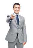 Happy smiling businessman in suit pointing at you Royalty Free Stock Photography