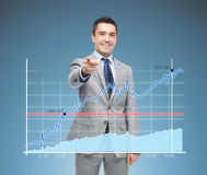 Happy smiling businessman in suit pointing at you Stock Image