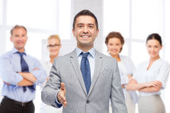 Happy smiling businessman in suit shaking hand Stock Photography