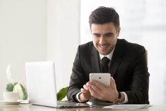 Happy smiling businessman using computer tablet, electronic devi. Happy smiling businessman using electronic devices at workplace for digital business management Royalty Free Stock Photo