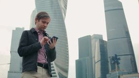 Happy smiling businessman wearing suit and using modern smartphone near office at early morning, successful employer to. Happy smiling businessman wearing black stock video