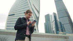 Happy smiling businessman wearing suit and using modern smartphone near office at early morning, successful employer to. Happy smiling businessman wearing black stock footage