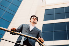 Happy smiling businessman wearing suit near office at early morning, successful employer to make a deal while standing near skyscr. Happy businessman wearing Stock Photo