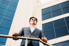 Happy smiling businessman wearing suit near office successful employer to make a deal while standing near skyscraper office. Happy businessman wearing suit near Stock Photo
