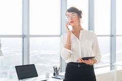 Happy smiling businesswoman having a business call, discussing meetings, planning her work day, using smartphone. Happy smiling businesswoman having a business royalty free stock photography
