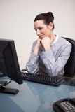 Happy smiling businesswoman sitting at her desk Stock Photography